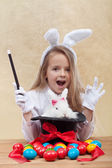 Little magician girl conjuring easter items — Stockfoto