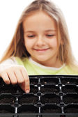 Little girl planting putting seeds into germination tray — Stock Photo