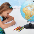 Little girl coloring the world map in geography class — Stock Photo #71033195