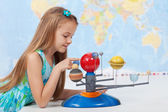 Little girl studies the solar system in geography class — Stock Photo