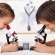 Young kids in science lab study samples under the microscope-foc — Stock Photo #71645797