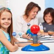 Geography class - little girl learning about the solar system — Stock Photo #72783377