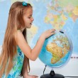 Young girl finding places on a globe — Stock Photo #72783439
