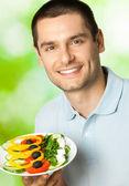 屋外のサラダのプレートと満足の笑みを浮かべて男 — ストック写真
