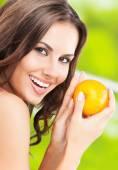 Ung kvinna med orange, utomhus — Stockfoto