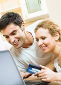 Cheerful couple paying by plastic card — Stock Photo