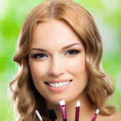 Smiling woman with make up tools, outdoor — Stock Photo