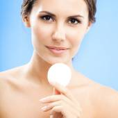 Young woman cleaning skin by cotton pad, over blue — Stock Photo