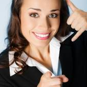Businesswoman with call me gesture, over blue — Stock Photo