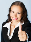Businesswoman with thumbs up, over blue — Stock Photo
