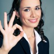 Happy business woman with okay gesture, over grey — Stock Photo #53766571