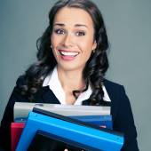 Businesswoman with folders, on gray  — Stock Photo