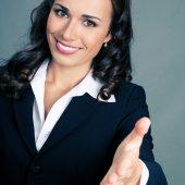 Podnikatelka dává ruku pro handshake, nad šedá — Stock fotografie