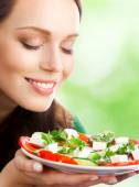 Portrait of happy smiling woman with plate of salad — Stock Photo