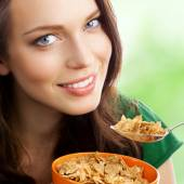 Woman eating muesli or cornflakes, outdoor — Stock Photo