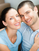Young smiling attractive couple at home — Stock Photo