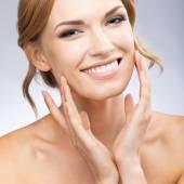 Woman touching skin or applying cream, on grey — Stock Photo
