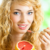 Young woman with grapefruit at home — Stock Photo