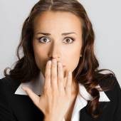 Business woman covering with hands her mouth, over grey — Stock Photo