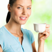 Young happy smiling woman drinking coffee, outdoors — Stock Photo