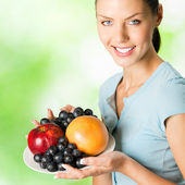 Young woman with plate of fruits, outdoors — Stock Photo