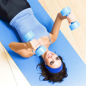 Young woman with dumbbells at home — Foto Stock