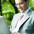 Young smiling businessman working with laptop — Stock Photo #56657167