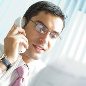 Businessman with phone and document at office — Stock Photo