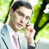 Hombre de negocios con ordenador portátil y teléfono móvil, al aire libre — Foto de Stock
