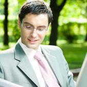 Empresario trabaja con ordenador portátil, al aire libre — Foto de Stock
