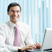 Businessman with laptop at office — Stock Photo