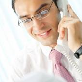 Businessman looking at document, with phone — Stock Photo