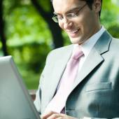 Young smiling businessman working with laptop — Stock Photo