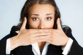 Business woman covering mouth, over blue — Stock Photo