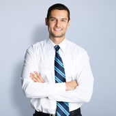 Happy smiling young businessman, against grey — Stock Photo