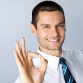 Businessman with okay gesture, against grey — Stock Photo