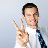 Businessman showing two fingers, against grey — Stock Photo