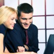 Two happy smiling young business people on laptop, working, chat — Stock Photo #58885721