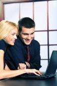 Two happy smiling young business people on laptop, working, chat — Stock Photo