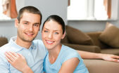 Young happy smiling attractive couple at home — Stock Photo