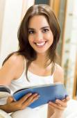 Cheerful young woman reading magazine, indoor — Stock Photo