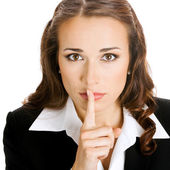 Portrait of young serious businesswoman keeping finger on her lips and asking to keep quiet, isolated — Stock Photo