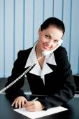 Businesswoman on phone signing document at office — Stock Photo