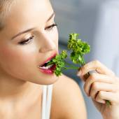 Woman eating coriander — Stock Photo