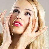 Beautiful young woman applying creme  — Stock Photo
