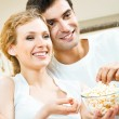 Couple eating popcorn and watching TV — Stock Photo #61636145