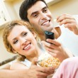 Couple eating popcorn and watching TV — Stock Photo #61636183
