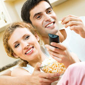 Couple eating popcorn and watching TV  — Stock Photo