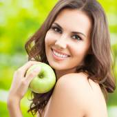 Woman eating green apple, outdoor — Stock Photo