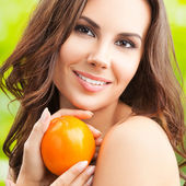 Woman with persimmon fruit — Stock Photo